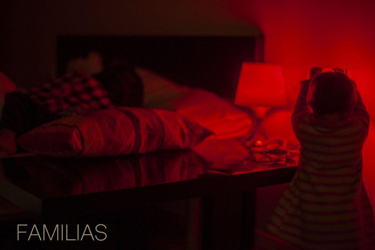 Familias, niño tocando una lampara en una habitación roja
